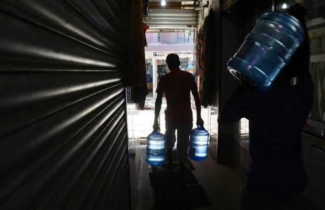 Sri Lankan laborers carry mineral water bottles at the main market in Colombo on October 29, 2013. (Lakruwan Wanniarachchi/AFP/Getty Images)