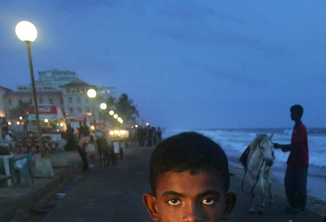 A Sri Lankan boy looks as he sells prawns at the sea front, in Colombo, Sri Lanka, Friday, June 30, 2006. (Manish Swarup/AP)